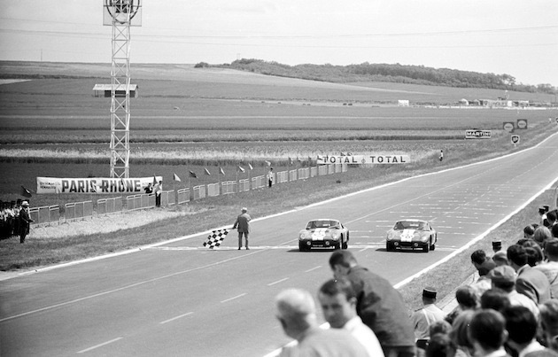 Reims 12 Hour Race, Reims, France, 1965. Two Shelby Cobra coupes cross the finish line together.